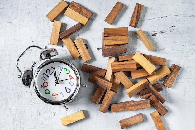 建設jengaタワーと木製テーブル上の時計