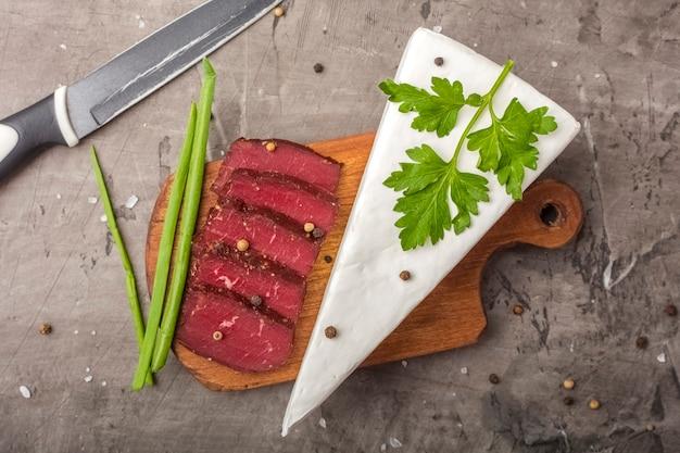 Вяленое мясо на деревянной разделочной доске и зеленом луке. мягкий сыр с белой плесенью