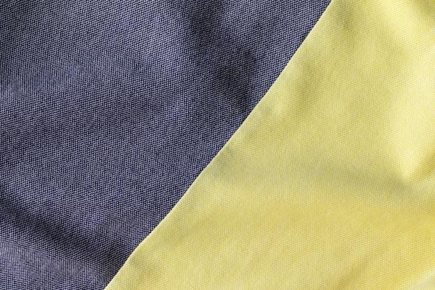 ジャージーコットン生地の風合い。しわくちゃの灰色と黄色のテキスタイルの背景