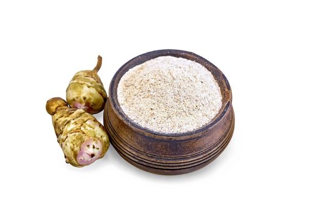 白い背景の上の明るい色合いの2つの塊茎とボウルにキクイモ粉