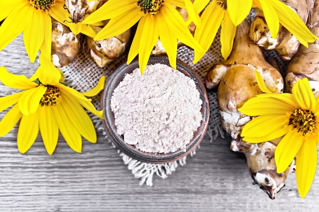 木の板の背景に花と黄麻布のボウルにキクイモ粉