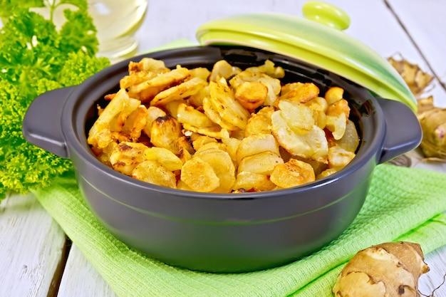Топинамбур, жареный на сковороде с крышкой, свежие клубни на салфетке, петрушка, растительное масло на фоне белой деревянной доски