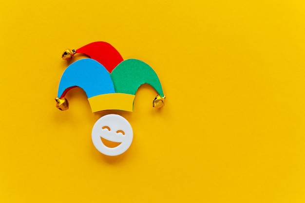 Jester hat with laughing face over yellow background first april card with emoji