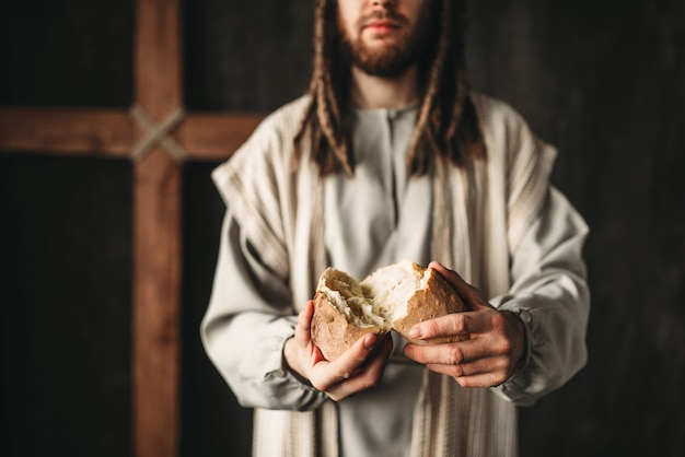 Jesus christ gives bread to the faithful, sacred food, crucifixion cross