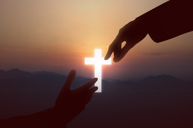 Иисус христос протягивает руку помощи человеку на фоне закатного неба