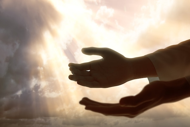 Jesus christ hand praying to god with a dramatic sky