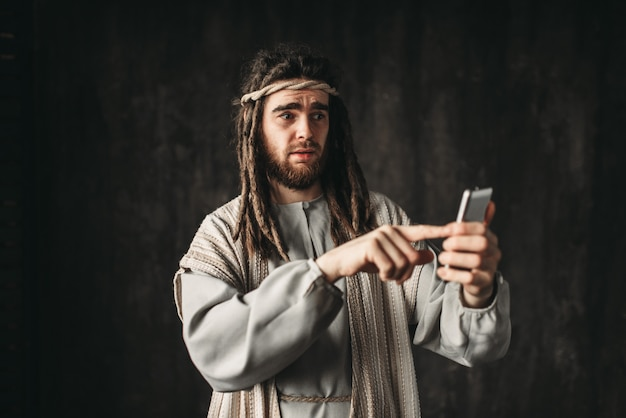 Jesus christ holds mobile phone on dark. gadgets from the evil one