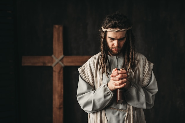 Jesus christ praying with bible in hands, cross on black