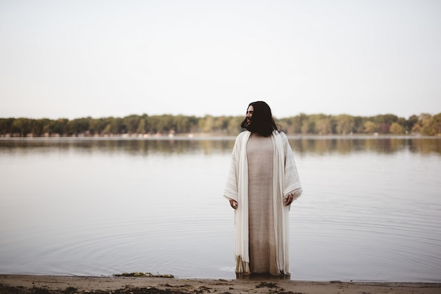 거리를 보면서 해안 근처의 물에 서있는 예수 그리스도