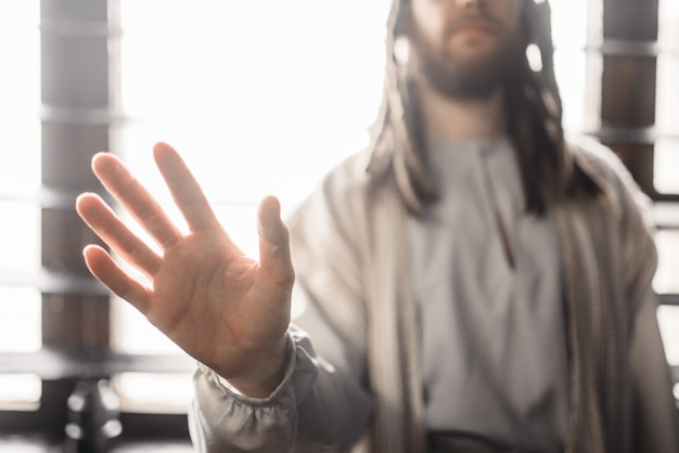 Jesus christ in white robe reaching out his hand,