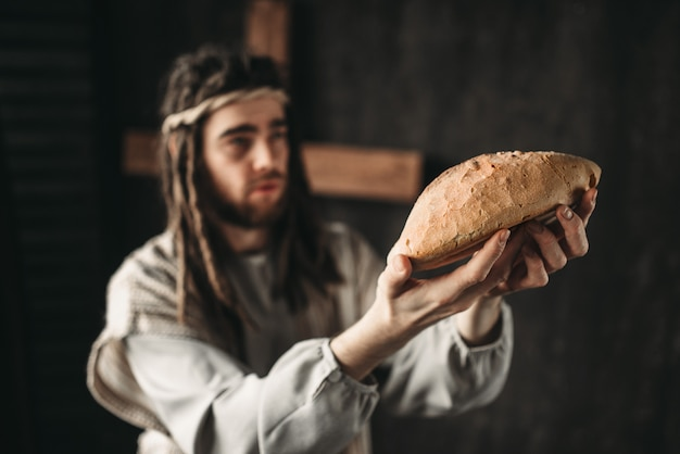 Jesus christ with bread in hands, sacred food, crucifixion cross