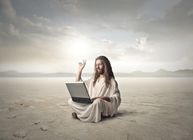 Jesus working on a laptop