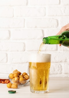 Jet of beer out of the bottle is poured into a beer glass, causing a lot of bubbles and foam, white brick wall background