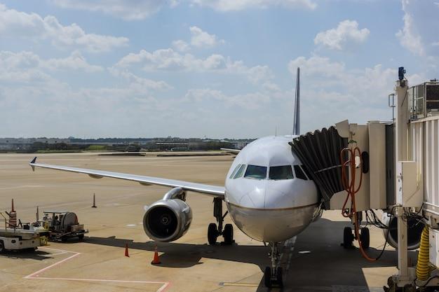 Реактивный двигатель против самолета среднего размера в аэропорту при загрузке самолета в международном аэропорту
