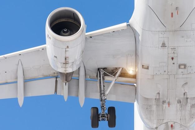 光沢のある金属製のジェットエンジン、フラップ付きの翼、ライトラバーホイールシャーシ、空港に着陸する前のクローズアップ。