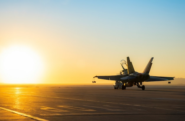 Jet fighter on an aircraft carrier deck against beautiful sunset sky .