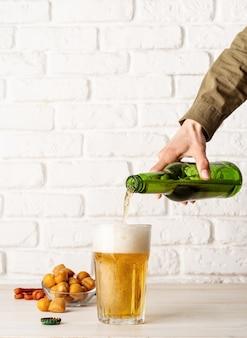 瓶から出たビールのジェットがビールグラスに注がれ、白いレンガの壁の背景にたくさんの泡と泡が発生する