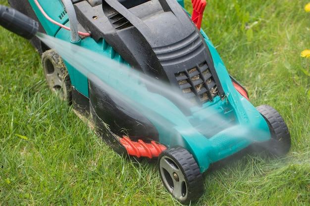 Струя воды из мойки высокого давления очищает грязную газонокосилку на зеленой траве