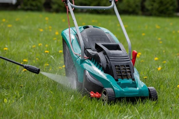 Струя воды из мойки высокого давления очищает газонокосилку на зеленой траве с желтыми одуванчиками. концепция садовых работ
