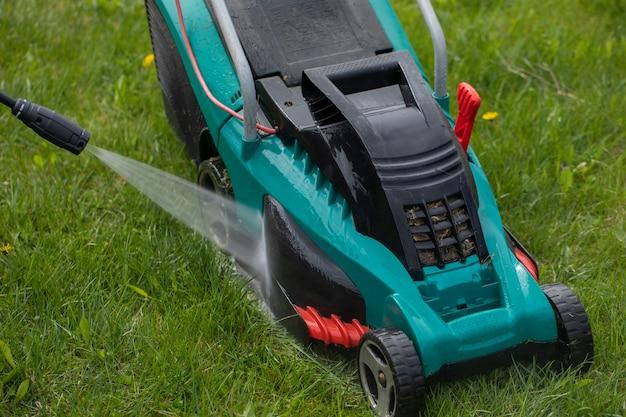 Струя воды из мойки высокого давления очищает газонокосилку на зеленой траве