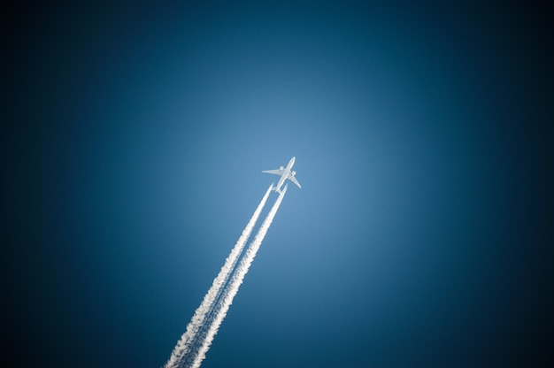 Jet plane flies in the blue sky and leaves a trail