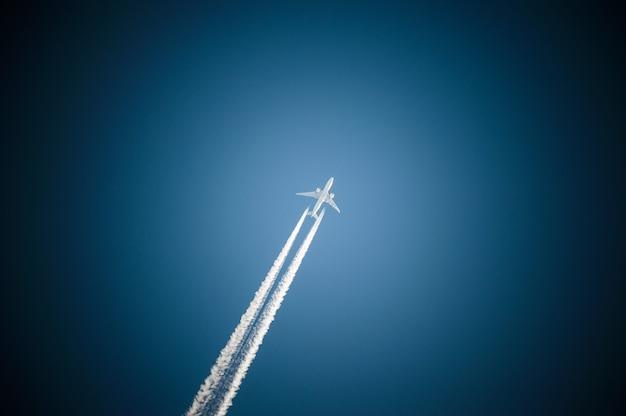 Реактивный самолет летит в голубом небе и оставляет за собой след