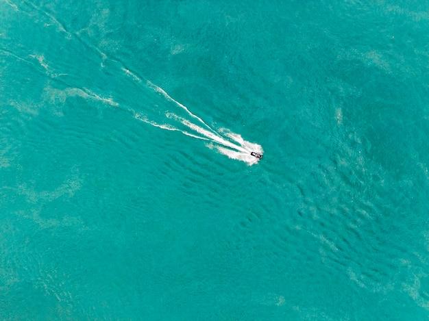 Катание на гидроцикле по воде вид сверху. морские развлечения на море. аквабайк в голубой воде озера или реки.