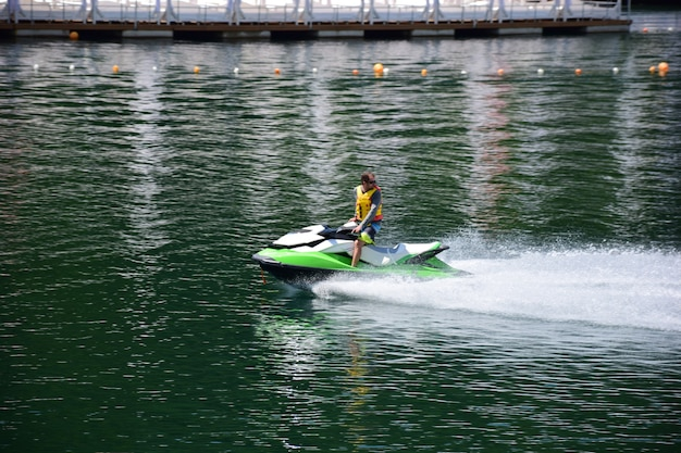 A jet ski with a man in a life jacket floating on it quickly rushes through the water