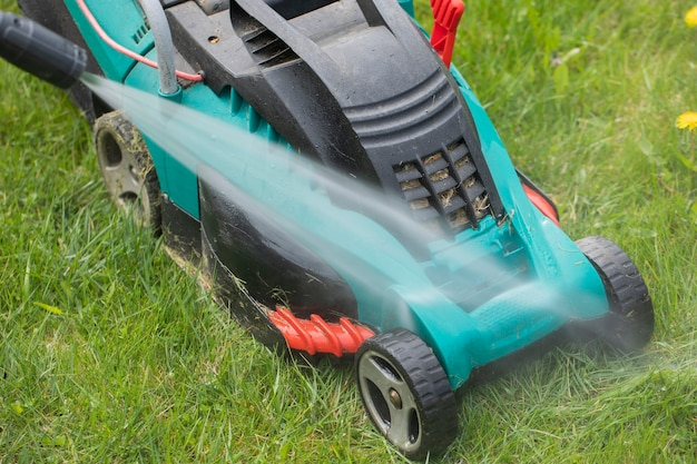 Jet of water from high-pressure washer cleans dirty lawn mower on green grass
