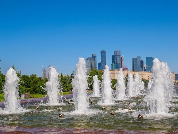 高層ビルと雲ひとつない青空を背景にした噴水の噴流