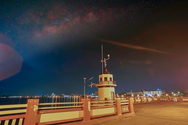桟橋には、星の中に灯台があり、街からのフレア光には淡い光があります。