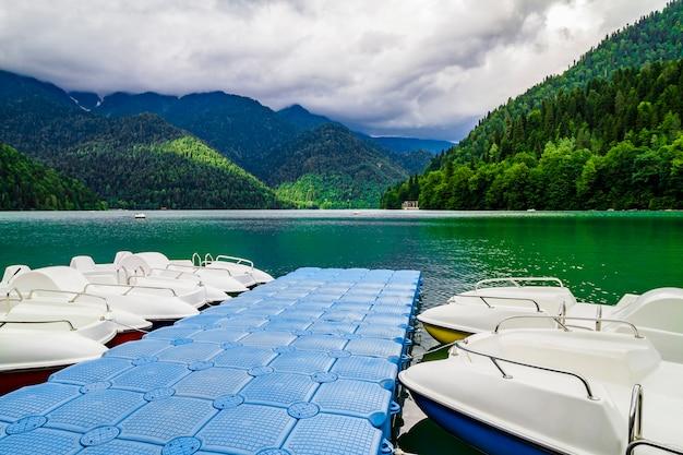 アブハジア自治共和国のritsa湖にある白いカタマランの桟橋。海岸に緑の松林の丘と山の湖