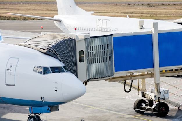 Jetway is served to passenger airplane at airport.