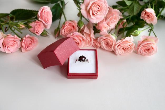 淡いピンクのバラに囲まれた、開いた赤いジュエリーボックスの宝石で飾られた婚約指輪。バレンタインデーを祝う