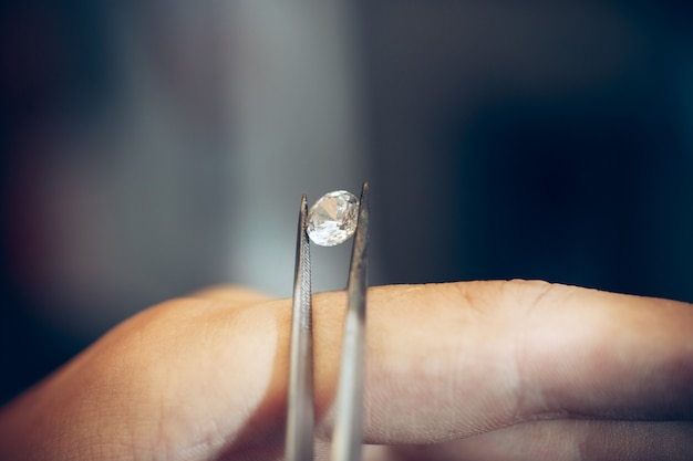 Jeweler holding diamond with  tweezers