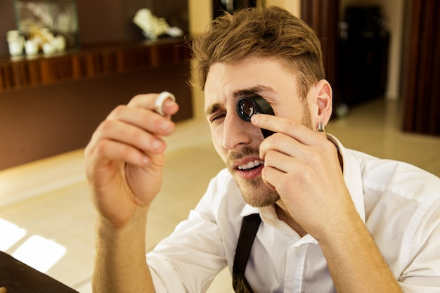 The jeweler holds a ring in his hands and looks at it through a magnifying glass.