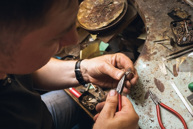 A jeweler removes details from a gold ring with precious stones in a workshop