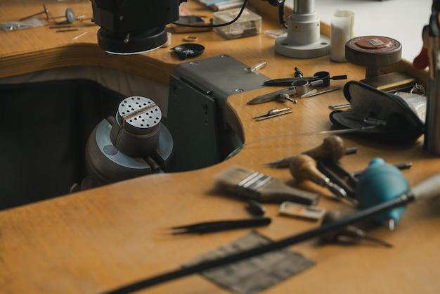 보석상 작업실. 나무 테이블에 다른 도구가 있는 보석상 작업대의 측면 보기. goldsmith 개념 배경