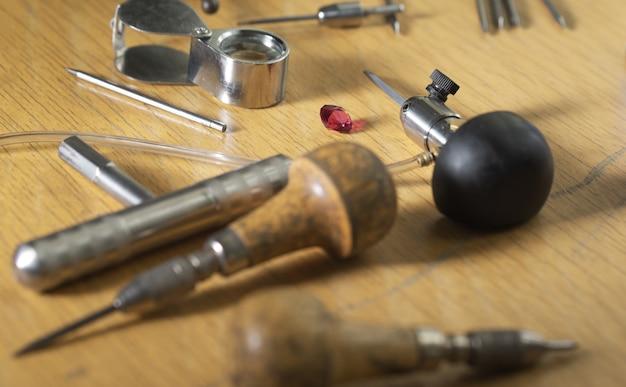 Рабочее место ювелира. инструменты и оборудование для ювелирных работ на старинном деревянном столе. ювелир, гравер за работой. сосредоточьтесь на драгоценном камне рубин