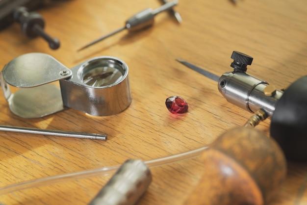 Рабочее место ювелира. инструменты и оборудование для ювелирных работ на старинном деревянном столе. ювелир, гравер за работой.