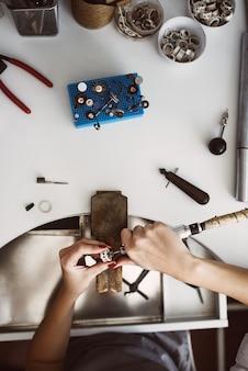 보석상 작업실. 흰색 테이블에 다양한 도구가 있는 보석상 작업대의 맨 위 보기. 새로운 보석을 만드는 여성의 손. 보석 장비. 작업 과정. 보석 제조 개념입니다.