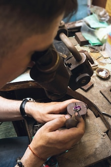 A jeweler using a microscope examines the defects of a gold ring