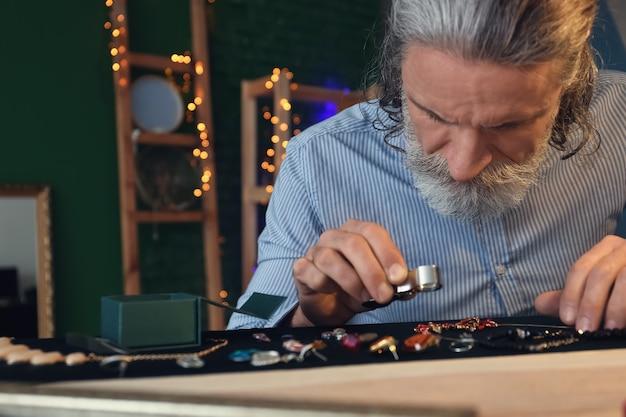 Ювелир рассматривает украшения в мастерской