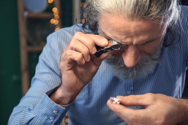 Ювелир изучает драгоценный камень в мастерской