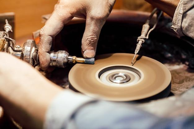 Jeweller polishing a stone blue cubic zirconia