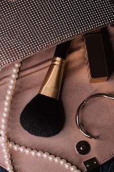 여성의 지갑, 미용 및 패션 근접 촬영 내부의 보석 및 메이크업 도구