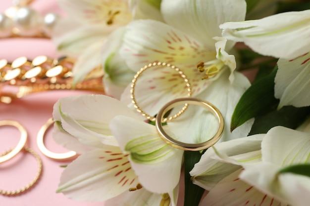 Ювелирные изделия и цветы на розовом фоне, крупным планом