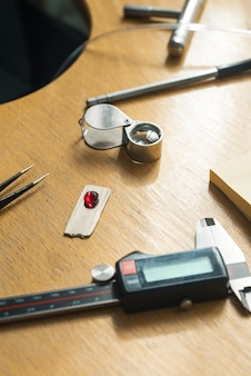 보석 장인 정신. 보석 핀셋, 돋보기, 루비 보석. 나무 빈티지 책상에 보석 조각사 도구입니다.