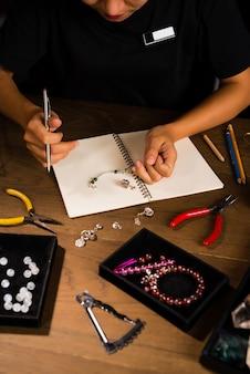 Дизайнер ювелирных изделий работает над эскизом чертежа руки