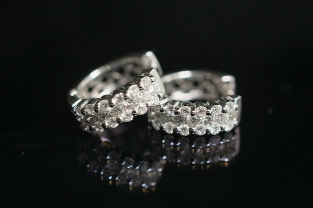 Ювелирные серьги с бриллиантами на черном фоне с отражением